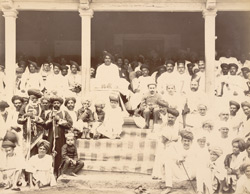 H.H.Shahu Chhatrapati Maharaj [sitting amongst crowds watching a wrestling match].